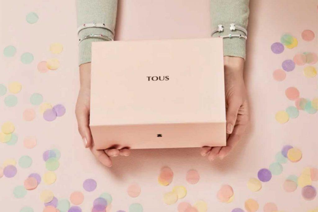 La imagen muestra las manos de una chica luciendo Joyas Tous mientras sostiene una caja de Tous