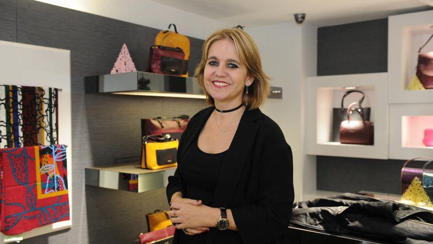 Rosa Tous posa en un establecimiento de la marca con diferentes modelos de bolsos Tous de fondo.